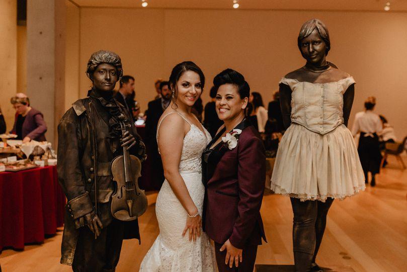 Newlyweds beside statues