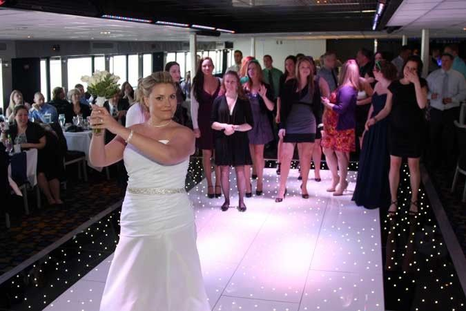 The Bride and her bouquet toss on the dance floor of the Spirit of Philadelphia, docked at Penns...