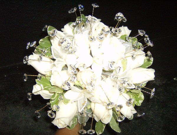 The White Wonders Bouquet 18 creamy white roses arranged to perfection. Bejeweled with crystals for...