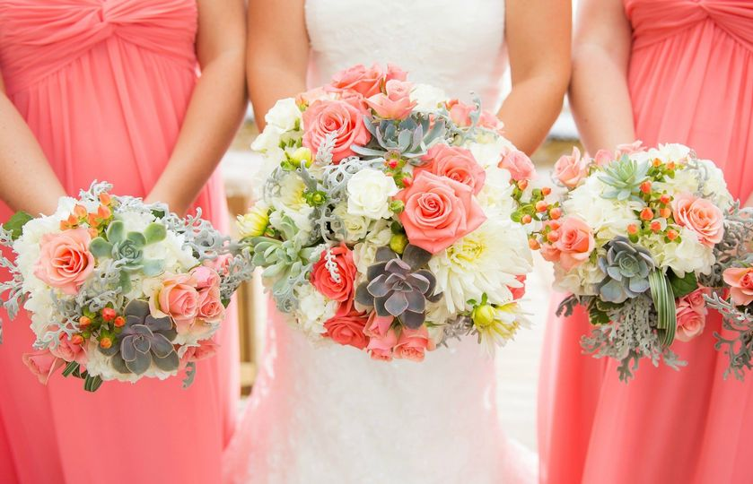 Coral roses and echeveria star in this hdntied bouquet.
