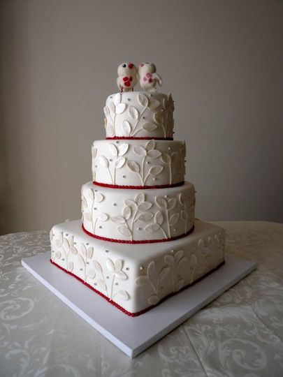 Elegant white fondant cake with luster leaves and silver dragees with red border.  The cake sizing...