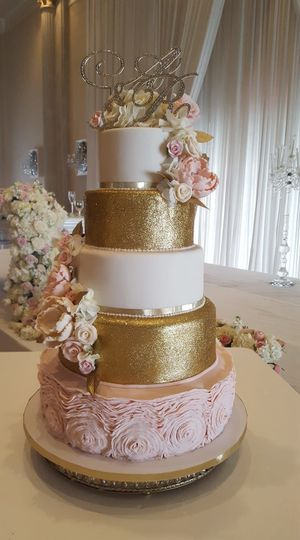 Lavish gold and blush ruffled 5 tiered wedding cake with all hand sculpted rhinestone centered...