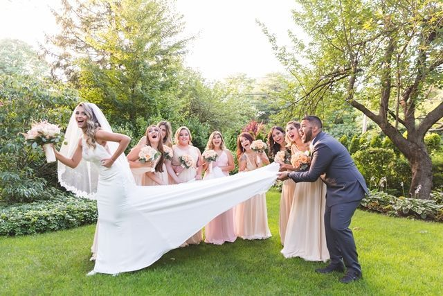 Bride's gown pulled by her groom and bridesmaid