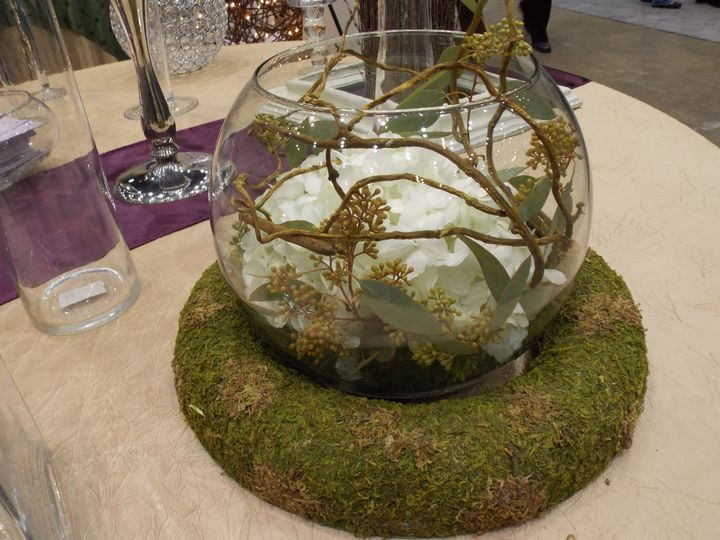A beautiful natural inspired centerpiece that rests in a moss covered ring.  Inside, submerged white...