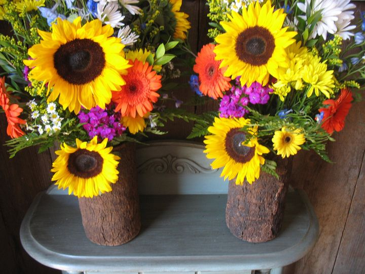 Bright sunflower and gerbera daisy alter arrangements in bark vases