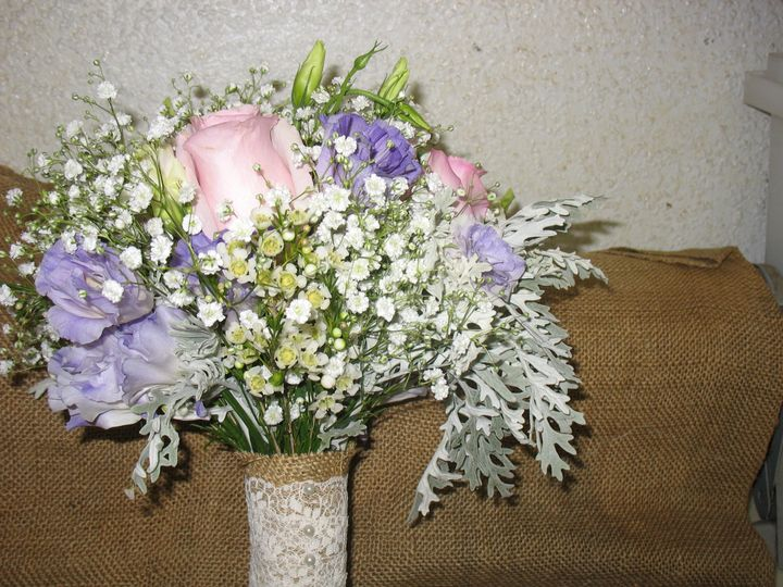 A bridal bouquet created with roses, lisianthus and babysbreath and fringed dusty miller