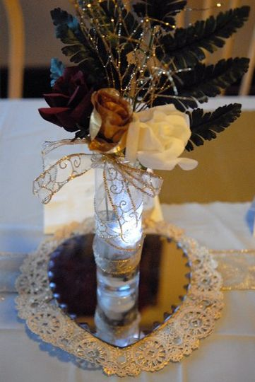 Flower centerpiece with burgundy, gold, and ivory flowers on heart shaped glass.