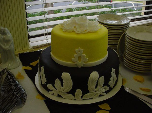 Wedding cake: Two tier covered in black and yellow fondant, accented with flowers, leaves and...