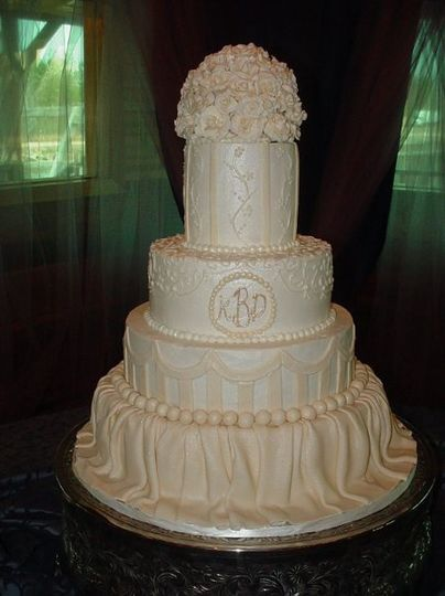 Wedding cake: Four tier buttercream with gumpaste flowers, fondant drappings and designs. Reception...