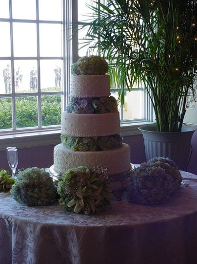 Three tiered buttercream with columns and designs, accented with hydrangeas. Reception held at King...