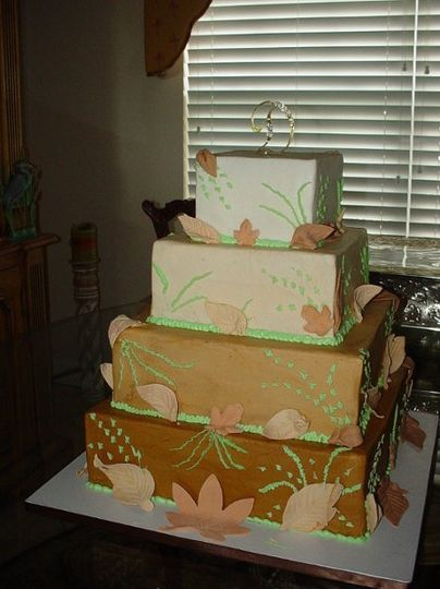 Four tier buttercream, in shades of brown to tan, with Fall design and gum paste leaves.