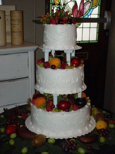 Three tiered column bettercream with scroll design accented with fresh fruit. Reception held at J...