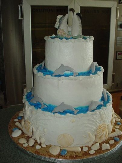Three tier buttercream accented with fondant dolphins and seashells.
