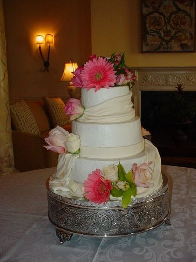 Three tier buttercream with fondant band and drapings accented with flowers. Reception held at King...