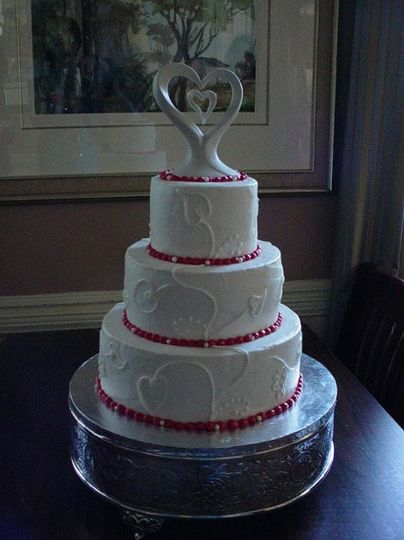 Three tier buttercream accented with heart design. Reception held in Fernandina Beach Fl.