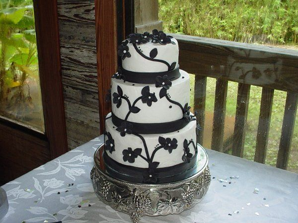 Wedding shower: Three tier buttercream with black fondant bands and flowers. Reception held at...