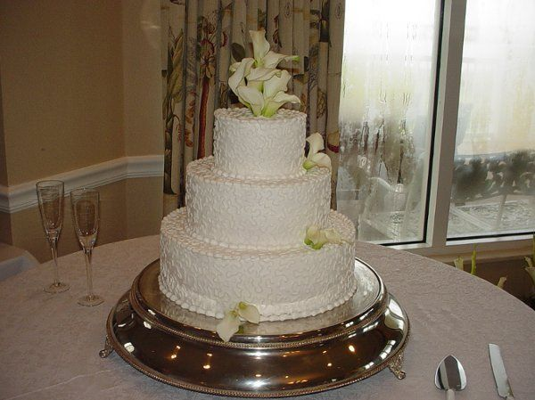 Three tier buttercream with lace design accented with calla lilies. Reception held at Epworth By The...