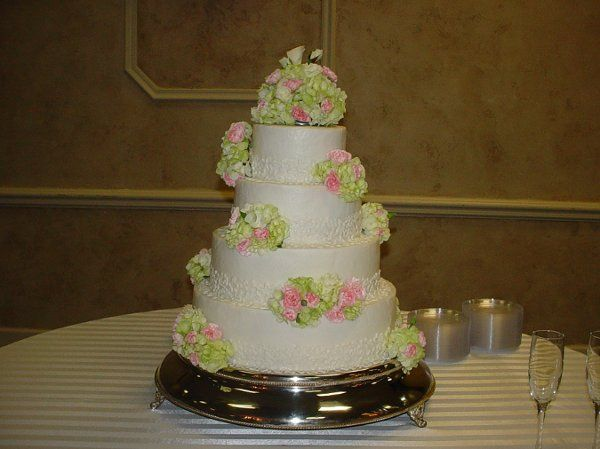 Four tier buttercream with bands of lace accented with flower arrangements, held at First Baptist...