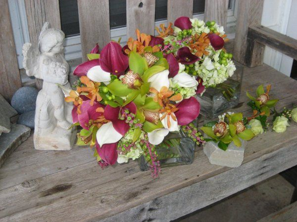 Green Cymbidium orchids, wine mini callas, white mini callas, and orange orchids