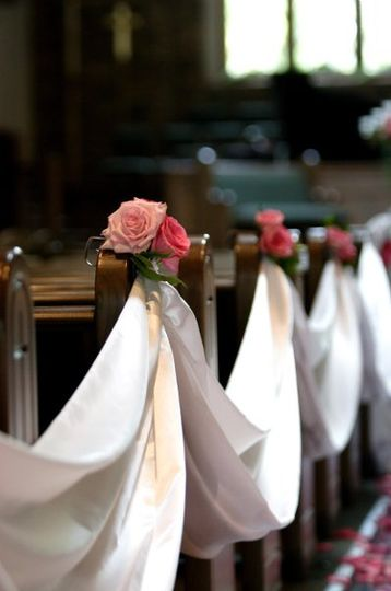 Aisle with fabric and flowers drapped on each pew....petals scattered