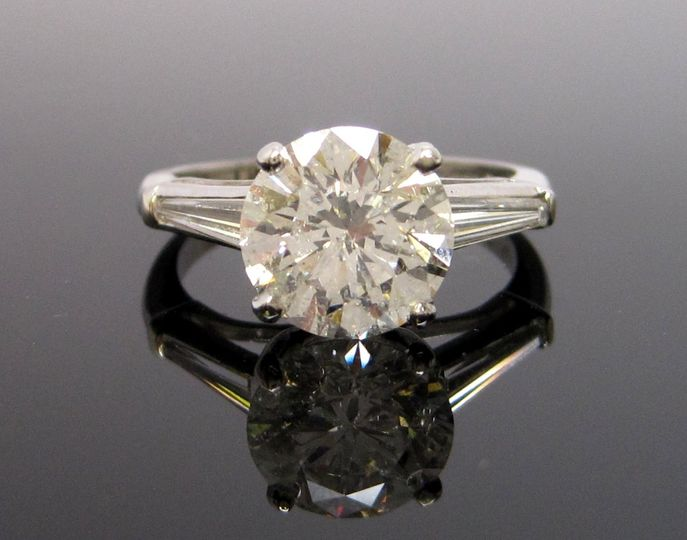 Lovely example of the classic Emerald cut diamond engagement ring. Shown is a certified 1+ carat...
