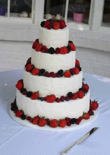 white buttercream textured for a rustic look and decorated with fresh summer berries.