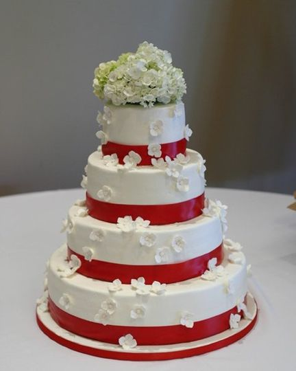 "white buttercream icing, this cake is decorated with sugar hydrangeas ""falling"" from the top tier."