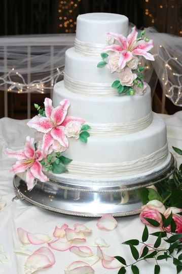 pleated white chocolate border and hand made sugar lilly's, roses, berries.