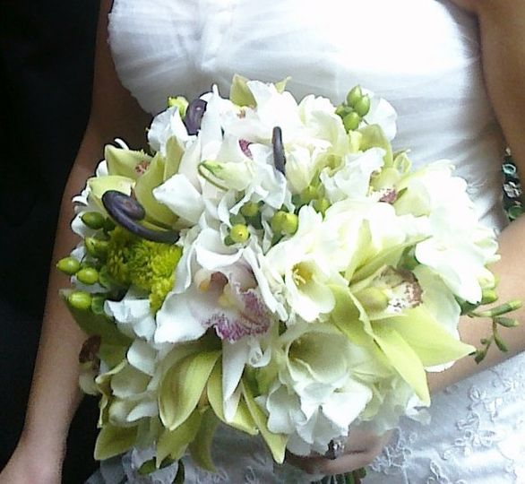 Green and white cymbidium orchids, white freesia, white sweet peas, hypericum and fern curls