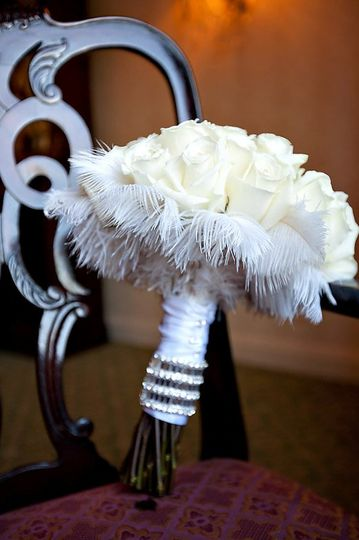 White roses are adorned with rhinestones and accented with white feathers. A crystal band is...