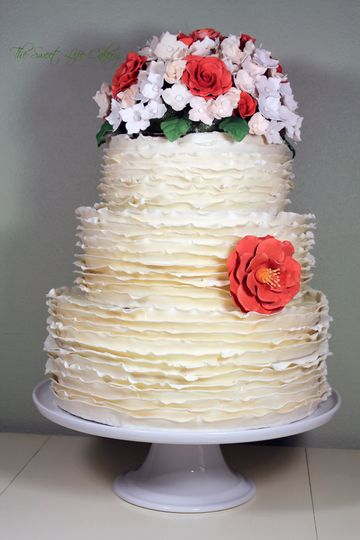 3 tiered cake covered in fondant ruffles with gum paste flowers