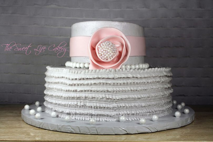 2 tiered cake covered in buttercream with fondant bow and edible pearls