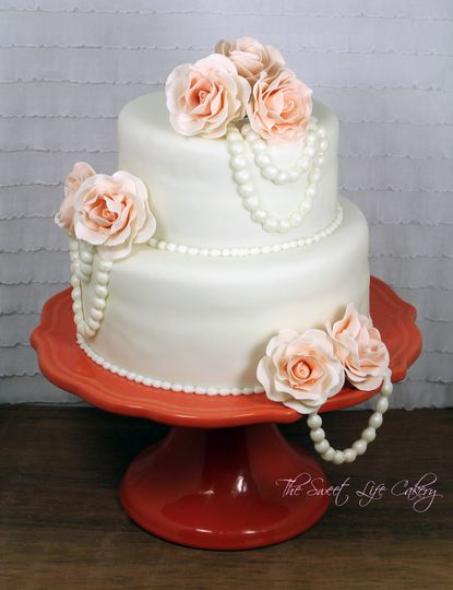 2 tiered cake covered in fondant with gum paste roses and pearls
