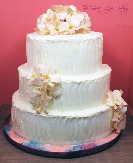 3 tiered cake covered in textured buttercream with freeze dried orchids