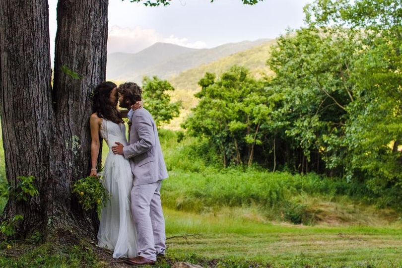 Newlyweds kiss by the trees