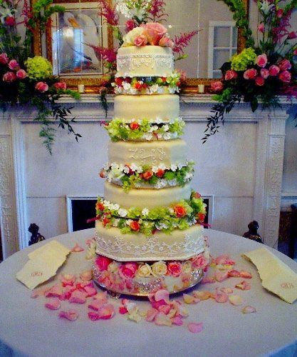 This fondant covered separated cake serves about 280 guests.  The piping matches lace on the bride's...