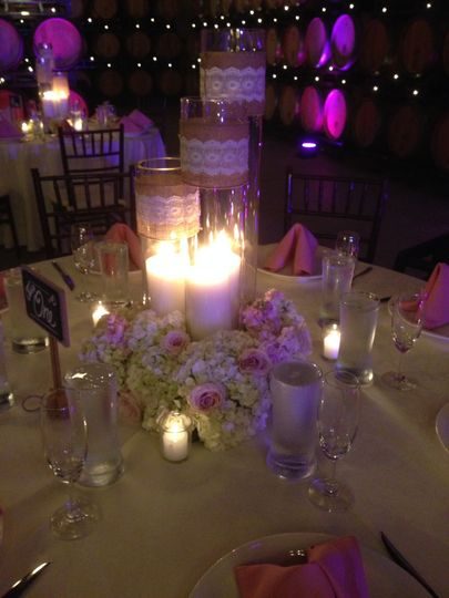 Candles in vases with hydrangea and roses at the base.