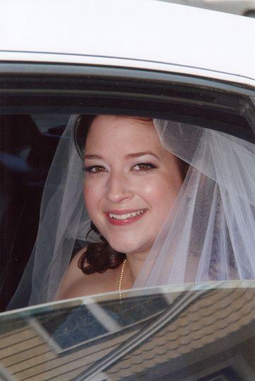 Bride peeking from inside the car