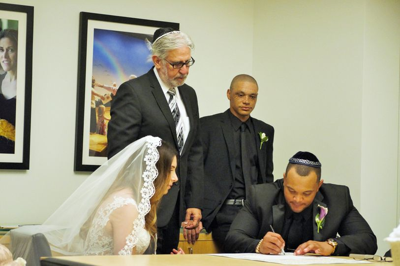Rabbi Michael Mayersohn has the bride and groom sign their Ketubah minutes before their Jewish &...