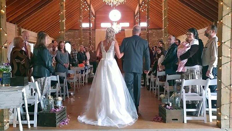 Father and Daughter walking down the isle together.