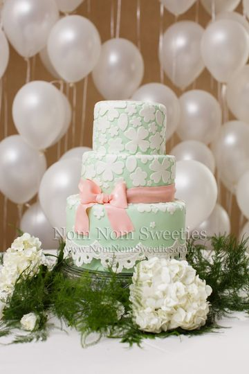 Mint green and coral wedding cake with edible details (floral overlay, ribbon, bow, and lace).