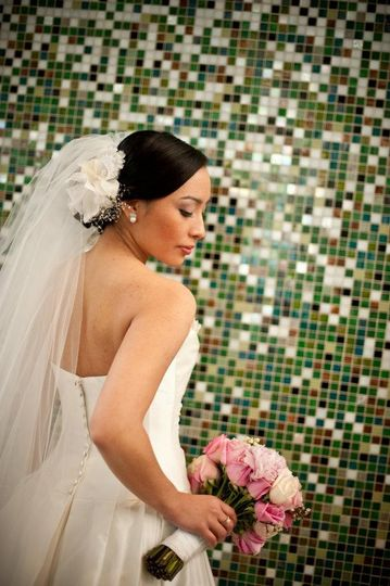 Flawless airbrush makeup and an elegant updo with classic side swept hair, keeps the bride looking...