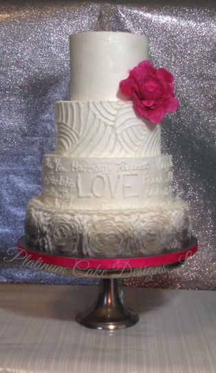 This 4-tier pearl white cake is decorated in all buttercream.  It has clean curvy piped lines,...