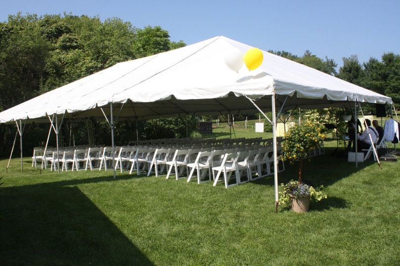 30' x 50' frame tent with white padded chairs for wedding ceremony.
