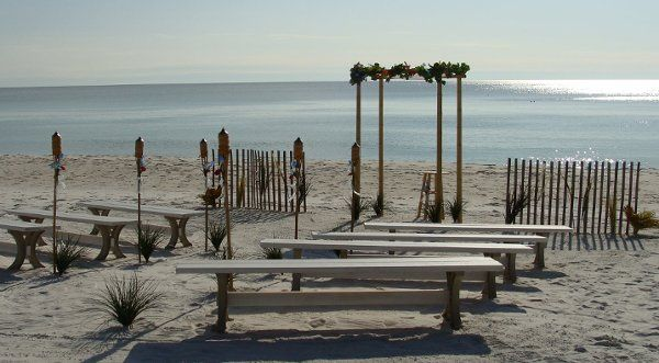 Natural bamboo arch with white canopy and flowers and white wedding benches.