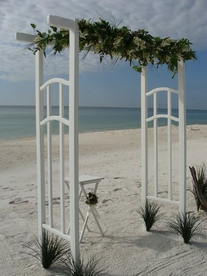 White arbor arch with unity sand table all with a view of the water