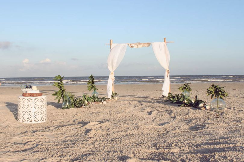 simple beach wedding with driftwood aisle and bamboo arch.