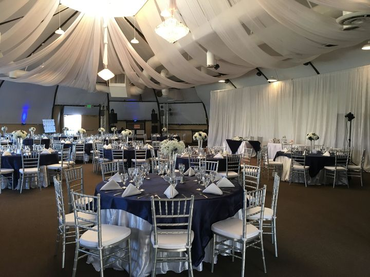 Navy blue overlays with satin white tablecloths