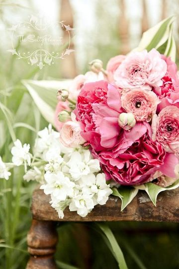 Pink and white bouquet of stock and ranunculus with hosta collaring.