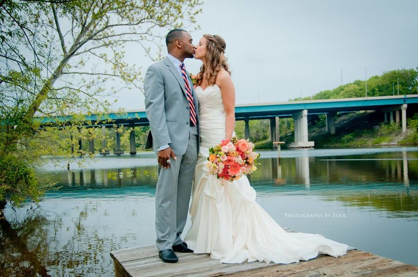 Newlyweds kissing by the water